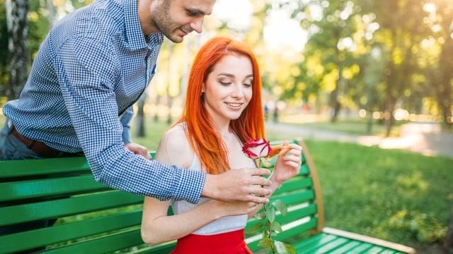 Mann steht hinter einer Frau und beschenkt sie mit einer Rose