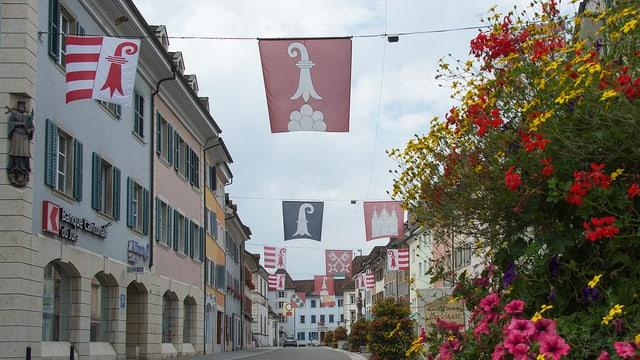 Strasse von Delemont mit Kantons- und Gemeindefahnen