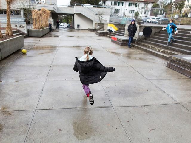 Ein Kind rennt über einen Platz