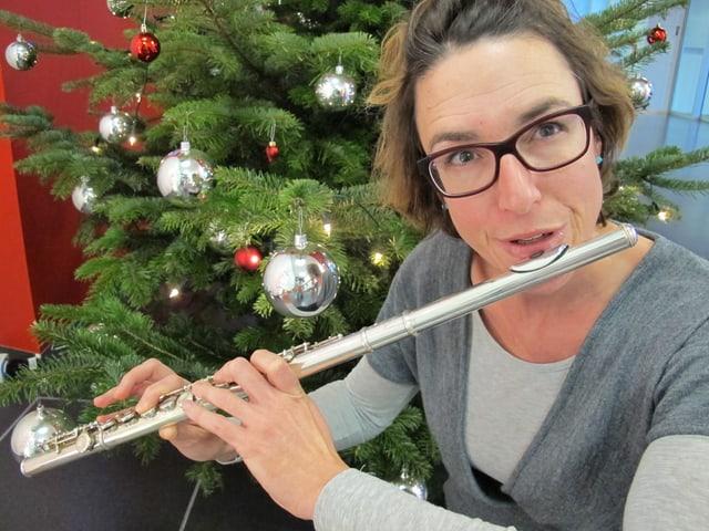 Joelle Beeler mit Querflöte vor dem Weihnachtsbaum.