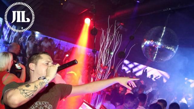 Ein DJ mit einem Mikrofon vor dem Mund, dahinter tanzende Party-Gäste, an der Decke eine Disko-Kugel.