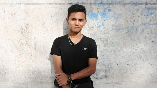 Ein Jugendlicher steht vor einer grauen Wand und blickt in die Kamera.