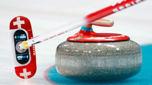Ein Curlingstein sowie ein Schweizer Besen