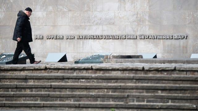 Purtret d'in um che passa dasper ina tavla da commemoraziun ora. Davostier sin la paraid stat scrit: «Den Opfern der nationalsozialistischen Gewaltherrschaft».