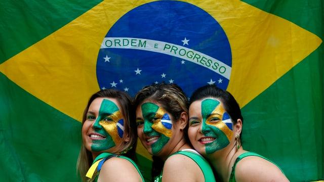 Drei brasilianische Fans posieren vor der Landesflagge