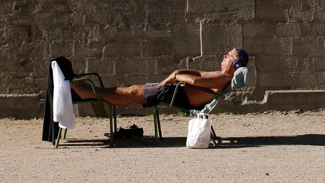 Mann in der Sonne auf Liegestuhl