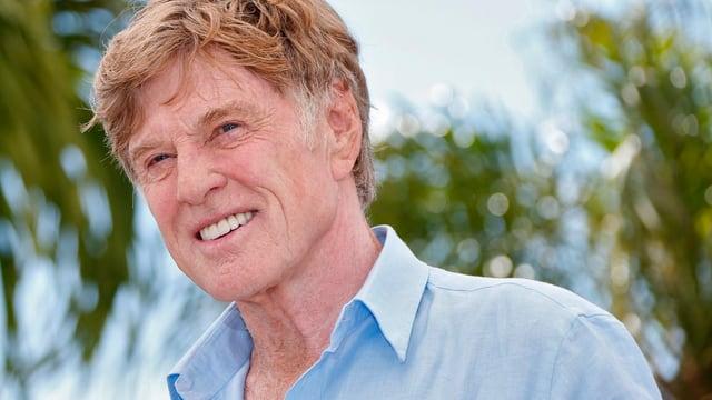 Robert Redford schaut im blauen Hemd der Sonne entgegen.
