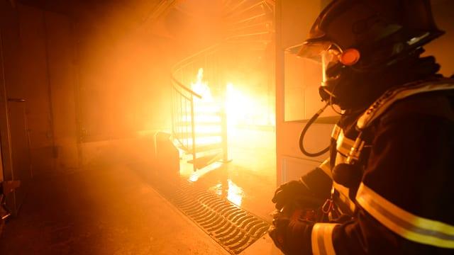Feuerwehrmann mit Atemschutzgerät in brennendem Haus.