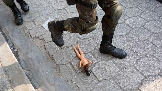 Ein Soldat steht knapp nicht auf eine nackte Barbiepuppe.