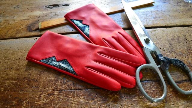 Ein paar rote Lederhandschuhe und eine Schere liegen auf einem Holztisch.