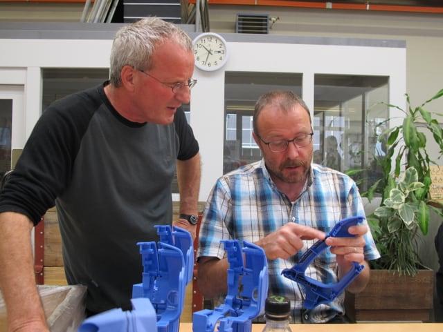 Rindlisbacher sitzt und zeigt einen blauen Plastikgriff der zusammen gesetzt wird.