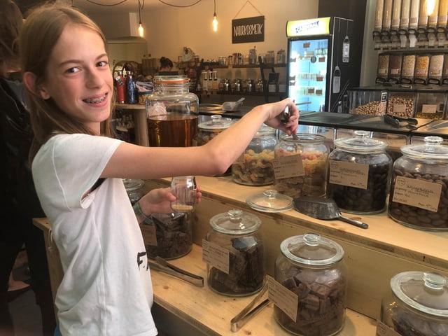 Raffaela nimmt Süssigkeiten aus den Behälter