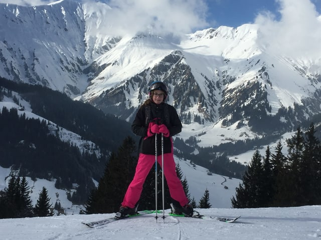 Mädchen steht rückwärts auf einem Berg