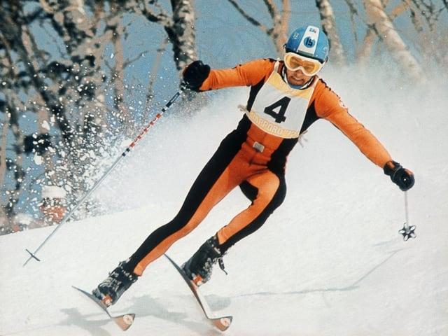 Bernhard Russi mit orangen Skianzug am Skifahren.
