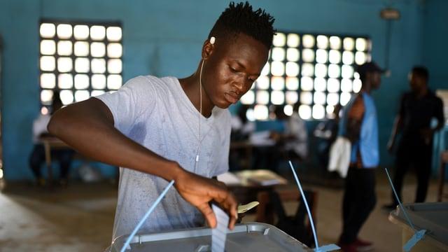 Junger Mann steckt einen Zettel in eine Wahlurne.