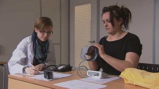 Eine Probandin prüft die Handhabung eines Blutdruckmessgeräts. Die beobachtende Expertin macht sich Notizen.