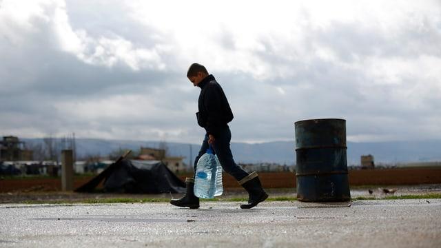 Ein Junge in Gummistiefeln trägt zwei grosse Wasserflaschen.