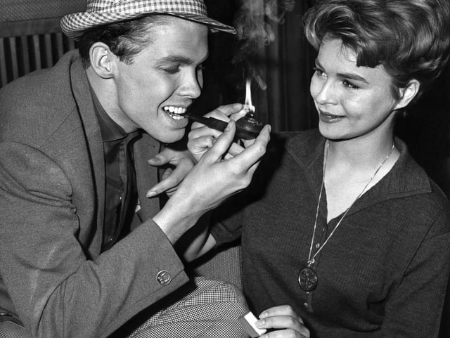 Conny zünden Peter während einer Drehpause eine Zigarre an.