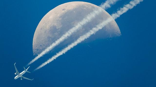 Ein Flugzeug hinterlässt Kondensstreifen vor dem Mond.