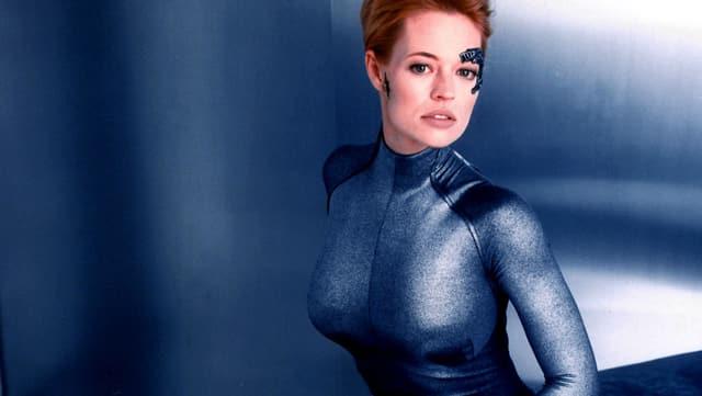 Sitzende Frau in eng anliegender blauer Kleidung. Über ihrem linken Auge sind technische Implantate zu sehen.