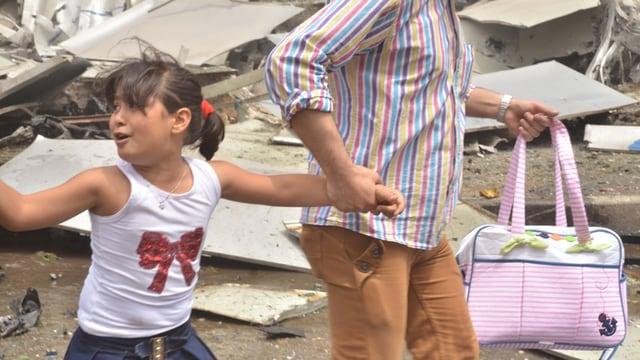 Frau hält in einer mit Trümmern übersähten Strasse von Aleppo ein Kind in weissem T-Shirt an der Hand