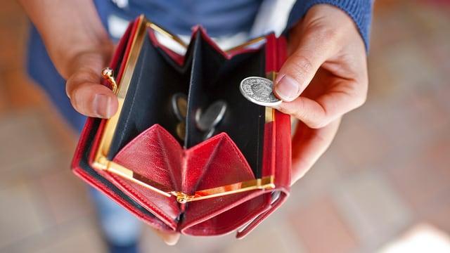Ein rotes Portemonnaie mit Münzen darin.