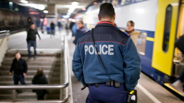 Ein Bahnpolizist überwacht Reisende auf dem Bahnsteig.