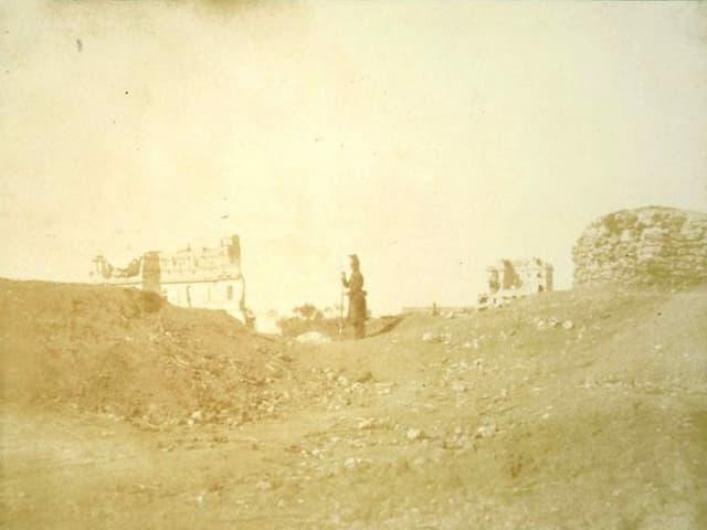 Alte Fotografie: Ein Soldat zwischen Ruinen.
