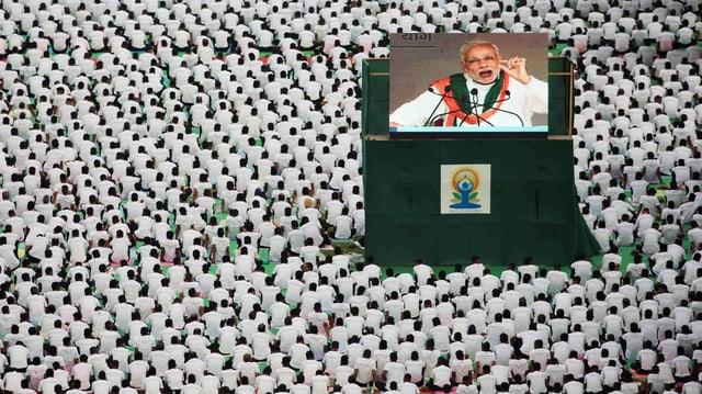 Wiese voll mit sitzenden, weiss gekleideten Menschen in Neu Dehli, in ihrer Mitte spricht auf einer Grossleinwand Premier Narendra Modi zu ihnen