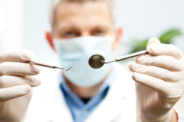 Ein Zahnarzt hält einen Spiegel und ein Diagnosewerkzeug vor die Kamera.