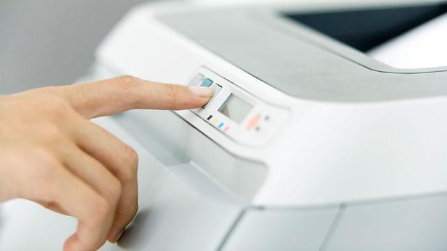 Eine Frau bedient eine Taste an einem Drucker.