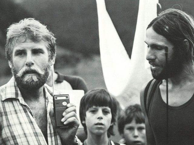 Schwarz-Weiss Foto von Markus Liechti und Kurt Saurer, die von ein paar Buben aufmerksam beobachtet werden.