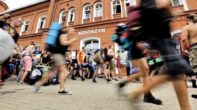 Viele junge Leute laufen auf einem Platz.