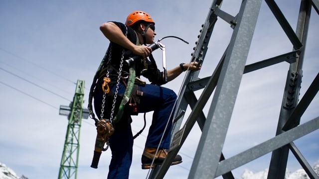 Ein Mann mit orangem Helm und Werkzeug klettert einen Seilbahnmast hinauf.