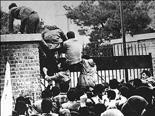 Studenten klettern über das Tor der US-Botschaft in Teheran, im Vordergrund eine Menschenmenge