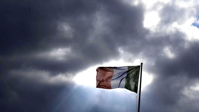 Ein dunkel bewölkter Himmel vor einer wehenden Italien-Flagge.