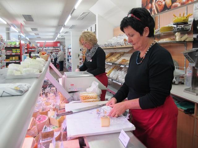 Frau mit schwarzem Hemd und roter Schürzer beim Käse einpacken.