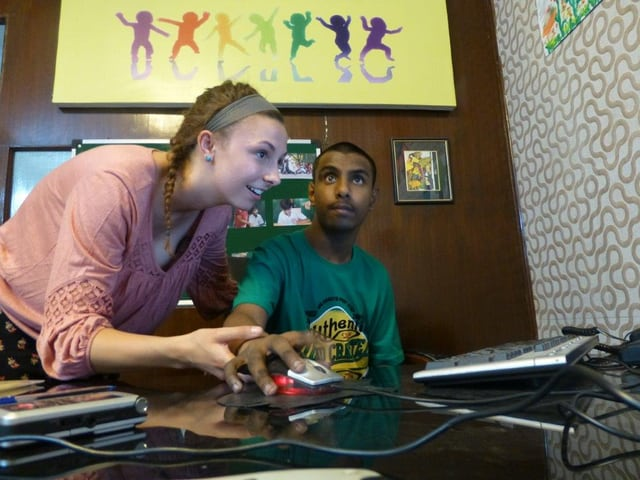 Eine weisse junge Frau hilft einem autistischen Inder am Computer.