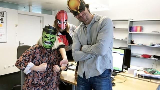 Drei unglaublich attraktive Superhelden posieren in einem unglaublich unattraktiven Büro.
