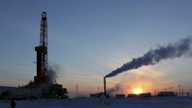 Ölbohrturm udn rauchender Schlot im Schnee bei Sonnenaufgang.