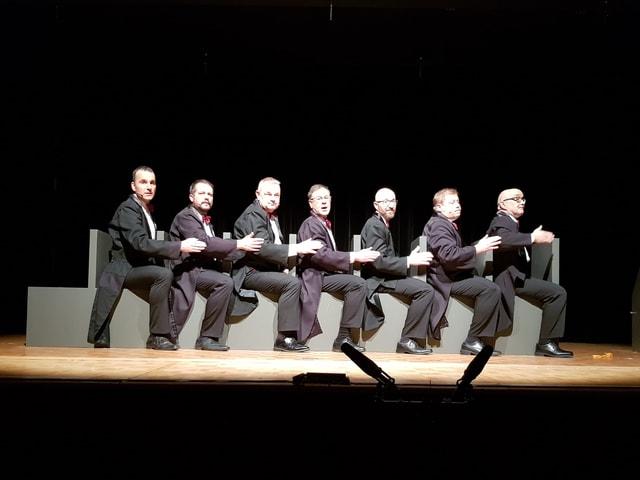 Sieben Männer im schwarzen Anzug sitzen hintereinander und singen.