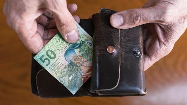 Zwei Hände, die eine Geldnote aus einem Leder-Geldbeutel nehmen.