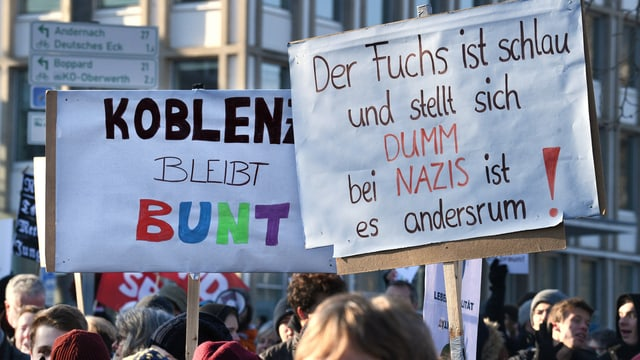 demonstrantas e demonstrants s'unischan cunter l'inscunter da populists en lur citad.
