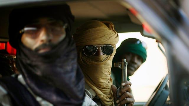 Drei bewaffnete Tuareg in einem Auto.