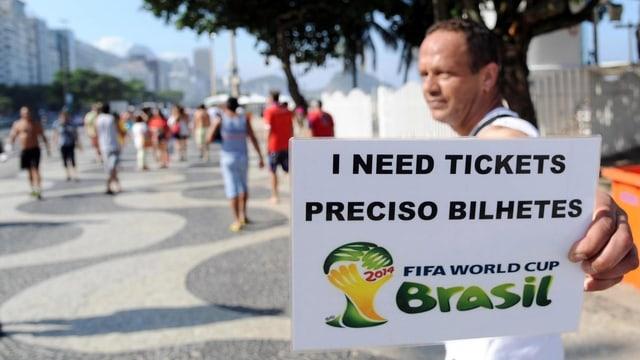 Mann an der Copacabana hält Schild mit der Aufschrift «suche Tickets» hoch