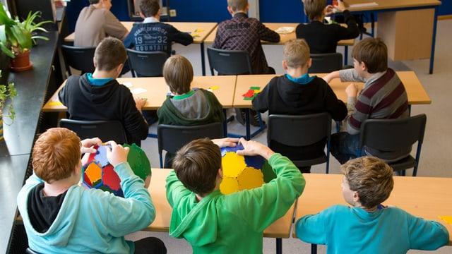 Ältere Kinder in einer Schulbank von hinten.