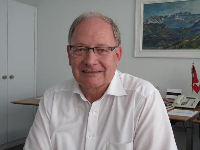 Wallimann sitzt mit einem weissen Hemd in seinem Büro. Er trägt eine Brille und etwas schütteres, graubraunes Haar.