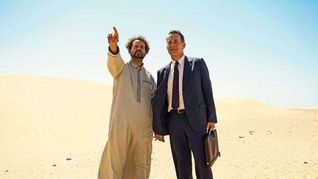 Tom Hanks als Alan Clay mit seinem Fahrer Yousef stehen in der Wüste.