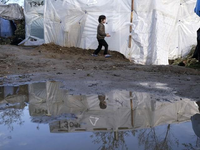 Ein Junge läuft an einer Zeltwand vorbei.