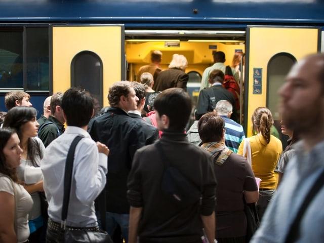 Pendler steigen in Zug ein.